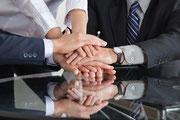 Mehrere Hände von Mitarbeitern auf einem Tisch übereinander