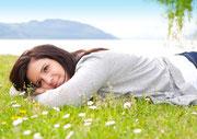Eine Frau liegt entspannt und etwas nachdenklich im Gras