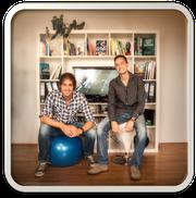 Henning und Nils zusammen vor dem Sportpsychologie-Regal