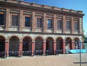 Schönes Backsteingebäude mit Schatten spendenden Arkaden
