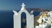 Der weisse Glockenturm auf einer kleinen Kapelle mit tiefblauem Meer