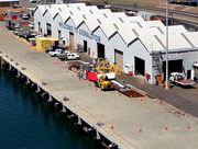 Einfache Bauten am Hafen heißen uns willkommen