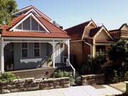 Vorbei an den typischen Häuschen mit Veranda zur Straßenseite