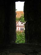 Blick durch eine Schiess-Scharte auf ein Gebäude ausserhalb der Ringmauer