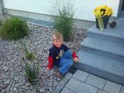 Seitlich der Treppe Pflanzung mit buntem Granitschotter bedeckt