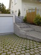 Rasenpflastersteine und bossierte Betonmauer