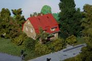 Gemütlich duckt sich das Siedlungshaus hinter den Büschen.