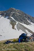 Wieder zurück nach der spannenden Kletterei: über das Schneefeld links vom Rucksack geht die Aufstiegsspur zur Felsnase und quert schließlich später nach rechts aufwärts