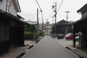 道標の付近、道路左、生垣に道標が見える