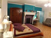 La grande chambre avec un grand lit de deux personnes...