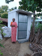 A beneficiary in front of a newly constructed private toilet.