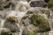 Kletterend water van een waterval op de bemoste stenen.