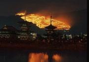 【1月若草山焼き薬師寺からの遠望】 若草山は、奈良公園の東端に位置する標高:342mの山で、三つの山が重なっていることから、三笠山ともいわれている。そのためか、関西ではどら焼きの形が三笠山に似ていることから、「三笠まんじゅう」や「三笠焼き」と呼ばれている。写真は、毎年1月に行われる山焼きで、1760年に東大寺と興福寺による領土争いが発端とも、若草山山頂にある前方後円墳の霊魂を鎮める祭礼とも、諸説がある。