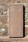 Grabplatte aus dem Ortstypischen Rotsandstein an der Aussenfassade der Kirche