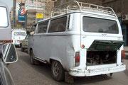 """Hier ist solch ein Taxi (Transporter) die Heckmotorklappe ist bei fast allen Fahrzeugen der Hitze wegen geöffnet. Der Verkehrslärm inklusive des konstanten """"gehupes"""" und des Abgasgestank´s ist grässlich."""