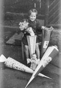 Angelika Hoffmann und viele Geschenke zur Einschulung im Jahr 1956 Dresden. Die Verwandschaft war groß und jeder brachte eine Zuckertüte mit. Es waren nicht nur Süßigkeiten darin, sondern auch Stifte und Radiergummis, Lineal und Dreieck, Tuschkasten und P