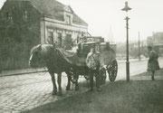 Fritz Hemesath mit seinem Eiswagen der Dortmunder Eiswerke auf dem Wambeler Hellweg, im Hintergrund der Turm der St. Liborius-Kirche -  Fotografie 1926-1930