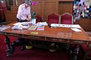 Geneviève Minssen s'affaire sur la table de conférence.
