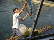 """""""Verkaufsfahrer"""": Auf einem kleinen Floß hakt sich der Mann am Schiff ein und verkauft während der Fahrt Fächer und anderes"""