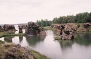 Lavasteinskulpturen von Kalfaströnd: Einzeln oder zusammenhängend und bewachsen ragen mehrere meterhohe Lavasäulen aus dem Wasser des Mývatn heraus.