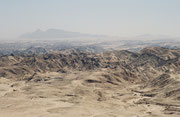 """Bei Swakopmund mündet der Swakob, einer der grössten zeitweise wasserführenden Trockenflüsse im Westen Namibias in den Südatlantik. Dort, wo er sich vor etwa 450 Mio. Jahren in weiche Gesteinsschichten gegraben hat, liegt heute die """"Mondlandschaft""""."""