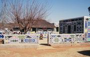 """Zum """"lebenden Museum"""" im Botshabelo Nature Reserve gehört auch ein bewohntes Ndebele Dorf. Die Häuser werden von den Frauen in individueller, unvergleichlicher Weise bemalt. Geometrisch dargestellt werden Alltagssituationen und -gegenstände."""