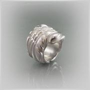 Schwerer Ring in Silber, die Oberflächenstruktur zeigt eine durch ein unsichtbares Band erzeugte Wicklung.