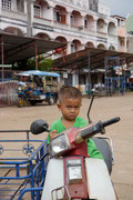 young boy reading to take on the streets of Pakse on his motorcylce!