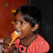 young Sri Lankan girl on train journey enjoying an ice cream