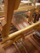 上田紬ができる折り機です。赤、黄のたて糸がはられています。