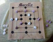 La merelle; petit jeu très couru au myen âge dont le but est d'aligner ses piuons pour soufler ceux de l'adversaire