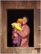 Una mujer sostiene sonriente a su hijo en un poblado de Kalaw. © Daniel Roca García.