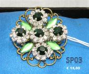 Filigrana tono oro con strass tono smeraldo e corona in strass bianchi. Quattro foglie il laminato verde agli angoli.