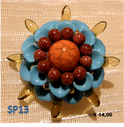 Fiore celeste in fimo con perle tono oro inserite tra i petali e perle in sabbia d'oro nella corolla, perla centrale in argilla