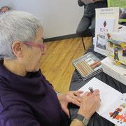 Evelyne Reine, illustratrice, qui dédicace un livre avec un dessin