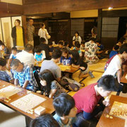 左端に立っていらっしゃるのが窪田空穂将棋教室の立役者山下先生。プロ棋士の先生とみんなが指せるように目をくばっていらっしゃいます。