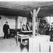 In der  Werkstatt. Louis und Karl Louwien, der mit einem Kollegen Zeichnungen studiert; Gesellen und Lehrlinge sowie zwei Kinder.