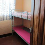 Four girls share a sleeping room. Each has a cabinet for storage of her personal belongings.