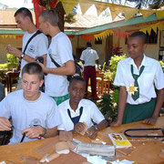 Tanzanian and german students while performing wood handcrafts together.