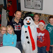 Some students with their teacher and a snowman on the market.