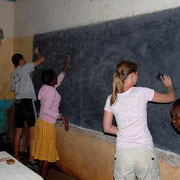 German and tanzanian students were working together to renew the classroom blackboards.