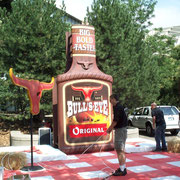 """BULL´S-EYE"" Giant BBQ Sauce Bottle and GIant Tablecloth. Designer, Sculptor, Scenic Artist. 2000"