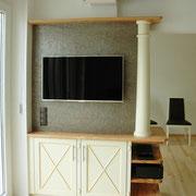 Eine besondere Fernsehwand: Olivenholz mit weiß lackierten und beige patinierten Fronten. Die Steinwand hinter dem Fernseher ist tatsächlich aus Stein - einer dünnen Schicht aus echtem Stein, die wir selbst verarbeiten und die den Raum beruhigt.
