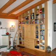 Ein massives Fichten-Regal nutzt die gesamte Raumhöhe und ist mit Hilfe der Leiter überall leicht zugänglich. Die Holzoberflächen sind gebürstet, gebeizt und lackiert.