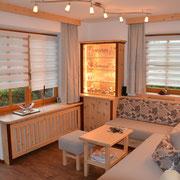 Dieses stimmungsvolle Wohnzimmer haben wir überwiegend aus Zirbe hergestellt. Die rötlichen Kontraste sind aus Kirschholz. Die gemütliche Couch verfügt über reichlich Stauraum in einer praktischen Schublade. Polsterung, Vorhänge und Licht durch uns.