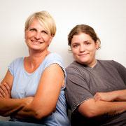 Zwei Frauen schauen selbstbewust in die Kamera.