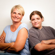 Zwei Frauen lächeln in die Kamera, lehnen sich aneinander und verschränken die Arme.