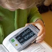Eine Frau benutzt ein Vergrößerungsgerät zum Lesen.