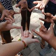Mehrere Hände bilden einen Kreis und zeigen das I love you-Zeichen.