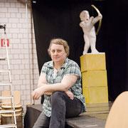 Eine Person sitzt auf einer Bühne und schaut in die Kamera. Hinter ihr steht eine Armorfigur.